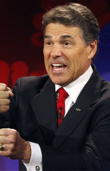 Republican presidential candidate, Texas Governor Rick Perry, gestures while answering a question at the CNBC Republican presidential debate in Rochester, Michigan, November 9, 2011.