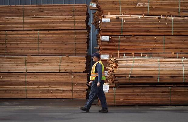 A worker walks past stacks of lumber at the Partap Forest Products mill in Maple Ridge, B.C.
