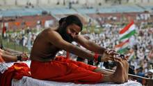 Some yoga teachers say the essence of the practise is inner peace and detachment from the world. But a growing wave of activists around the world are yoking yoga to politics – including guru Baba Ramdev, who led an anti-corruption protest (and a mass yoga session) in New Delhi this week. (RAJESH KUMAR SINGH/ASSOCIATED PRESS)