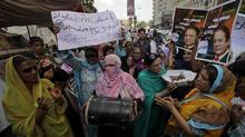 Supporters of Pakistan Muslim League-N (PMLN) hold images of their party leader Nawaz Sharif as they chant slogans and beat drums to celebrate the Supreme Court's decision against Prime Minister Yusuf Raza Gilani during a rally in Karachi June 20, 2012. (Akhtar Soomro/Reuters)