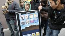 Lyle Kahmey, 9, wears an iPad billboard that he and his mother painted, as he waits in line to buy an iPad on the first day of Apple iPad sales at an Apple Store in San Francisco, Saturday, April 3, 2010 (Paul Sakuma/(AP Photo/Paul Sakuma))