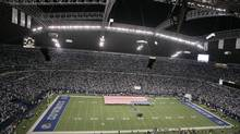 The pre-game ceremony with a giant American flag is presented at Texas Stadium under its famed roof with a hole before an NFL football game, Sunday, Dec. 14, 2008, in Irving, Texas. (Anonymous/AP)