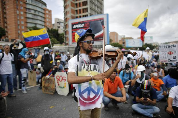 Image result for venezuela -- Wuilly Arteaga plays violin during an anti-government march in Caracas, Venezuela., photos