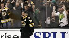 Fans celebrate with Boston Bruins' Andrew Ference after he scored against the Washington Capitals during the second period of an NHL game in Boston, Saturday, March 16, 2013. (Winslow Townson/AP)