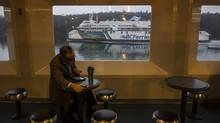 A Tsawwassen-bound BC Ferry passes a Swartz Bay-bound ferry December 9, 2013, unnoticed by a passenger intent on using his mobile devices. (John Lehmann/The Globe and Mail)