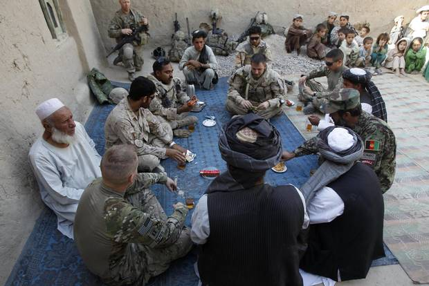 Canadian , US and Afghan army officers sit with local Afghan elders during a meeting in the village of Small Loi Kola in the Panjwai district, in the province of Kandahar June 23 , 2011. Canada will end its combat role in Afghanistan by the end of July, after nearly ten years fighting in the country.