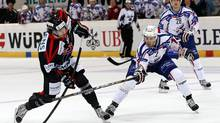 Fribourg's Julien Sprunger, left, vies for the puck with Adler Mannheim's Matthias Plachta, right, during the game HC Fribourg Gotteron against Adler Mannheim at the 86th Spengler Cup ice hockey tournament, in Davos, Switzerland, Saturday, Dec. 29, 2012. (Salvatore Di Nolfi/AP)