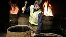 A cooper rebuilds oak casks at the company's traditional cooperage at Carsebridge, Scotland. The casks, recycled from previous use, will be used to store Diageo's scotch whisky. (Mike Wilkinson)