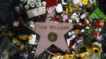 Flowers are seen on the late Robin Williams' star on the Hollywood Walk of Fame in Los Angeles, California August 12, 2014. Comedians, politicians and several generations of fans collectively mourned on Tuesday the death of Robin Williams, the actor famous for his frenetic and freewheeling comedy whose apparent suicide at age 63 prompted an outpouring of tributes. (LUCY NICHOLSON/REUTERS)