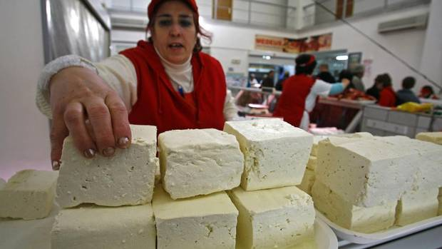 A woman arranges a piece of traditional Romanian cheese at Obor market in Bucharest. The Canadian government is preparing to raise its protectionist drawbridge and admit more European cheese into this country in return for greater access to EU markets for Canada's beef and pork. (BOGDAN CRISTEL /REUTERS)